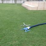 緑の芝生の上に2つの青いスプリンクラー。