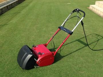 赤い芝刈機のアップ。斜め前から。芝刈後の芝生の緑を背景に。