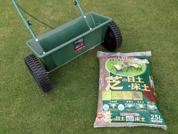 芝生の上の散布機と目土。刀川平和の芝の目土・床土、約25L。