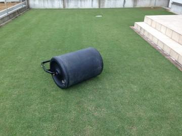 芝生の上の黒いローラー。バロネスの芝生専用転圧ローラー。