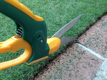 芝生のエッジを切る芝刈りバサミ。反対側から撮影。