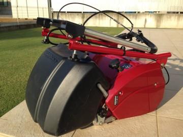ハンドルを折りたたんだ芝刈機。タイルデッキと芝生を背景に。