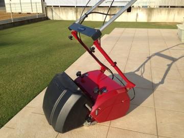 ハンドルを折りたたむ途中の芝刈機。庭のタイルデッキで撮影。