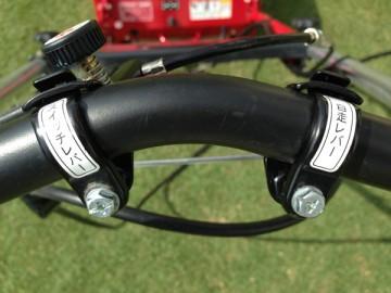 芝刈機のハンドル。「スイッチレバー」と「自走レバー」の表記。