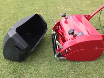 赤い芝刈機から取り外された、黒い樹脂製集草箱。
