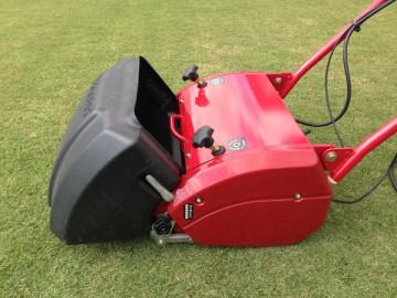 赤い芝刈機に取り付けられた、黒い樹脂製集草箱。