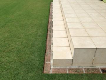 芝生の周囲に敷かれたレンガ。タイルデッキの周り。