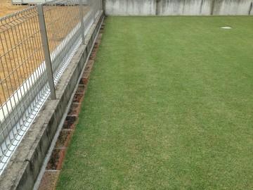 芝生の周囲に敷かれたレンガ。フェンスの内側。
