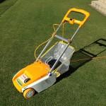 黄色い芝刈機、リョービ LM-2800。緑の芝生を背景に。