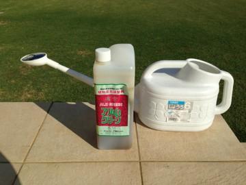 2Lのアルムグリーンのボトルと6Lのじょうろ。芝生を背景に。