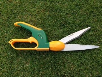 緑の芝生の上に置かれた黄色と緑の回転式芝刈りバサミ。