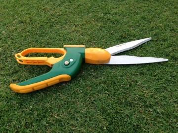 芝生の上の回転式芝刈りバサミ。刃と水平になった持ち手。