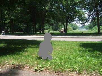 森の前の芝生にしゃがんでいる子供のシルエット。