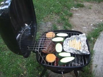 小さなバーベキューコンロで肉と野菜を焼いている。