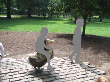 パブリック・ガーデンのカモの親子の銅像に座って写真を撮る子供たち。