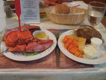 テーブルの上の丸ごとのロブスターと、ポテト、野菜、パン。