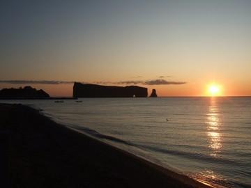 海からの日の出。逆行の朝日のなかの黒いペルセ岩。