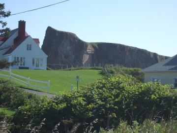 芝生、赤い屋根の白い家が1軒、その後ろに巨大な岩。