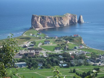 山の上からみたペルセの町とペルセ岩。町の一面に緑の芝生。