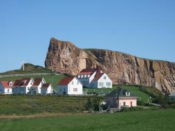 芝生の中に、赤い屋根の白い家が数軒、その後ろに巨大な岩。