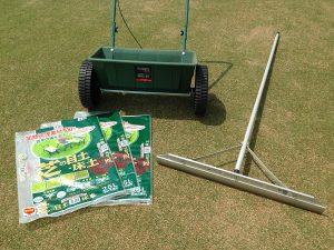 芝生の上のドロップシーダー、トンボ、目土の袋。