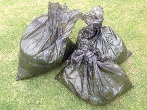 刈り芝の入った3つの黒いゴミ袋。