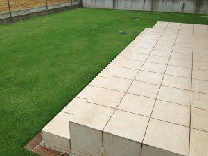 雨降に濡れたタイルデッキと芝生。