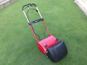 芝生の上の赤い芝刈り機、バロネスLM12MH。