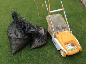 芝生の上のリョービLM-2800とサッチの入った黒いゴミ袋。