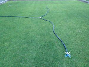 芝生の上のタカギのトリプルアームスプリンクラー。