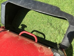 赤い芝刈り機、緑の刈り芝が黒い集草箱に一杯。
